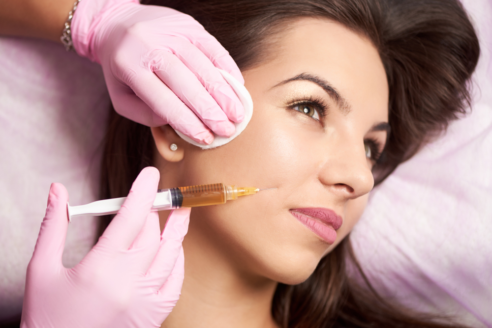 woman looking away receiving facial injections