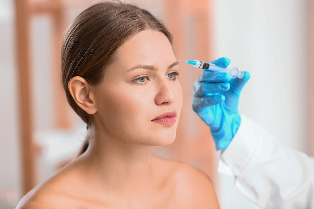 woman receiving eyebrow injection