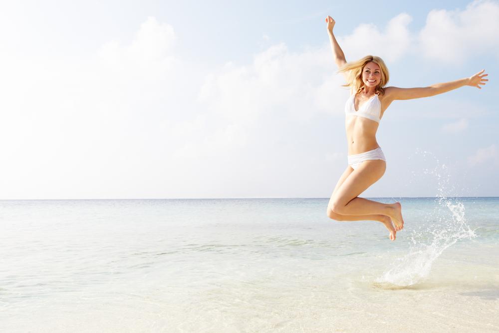 woman smiling jumping at beach