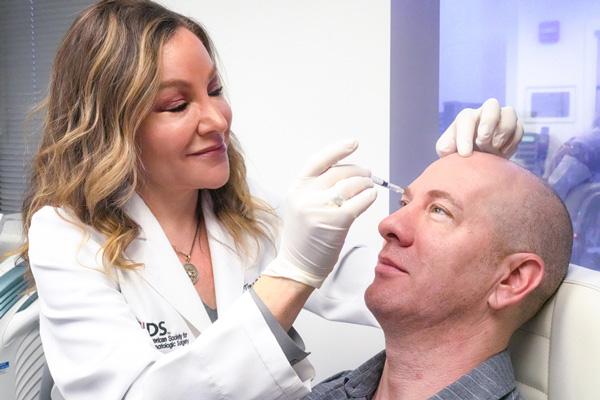 Dr. West injecting patient
